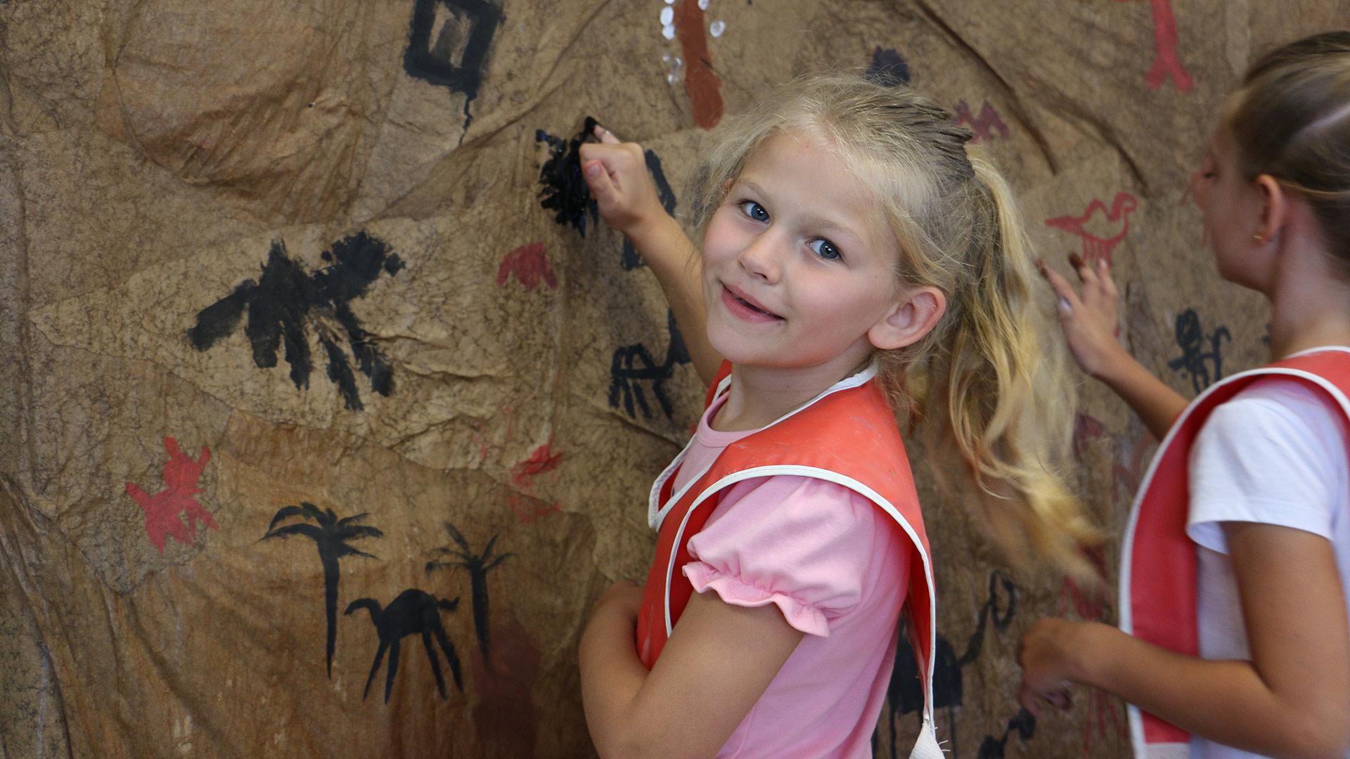 A girl painting on a large piece of paper on a wall.