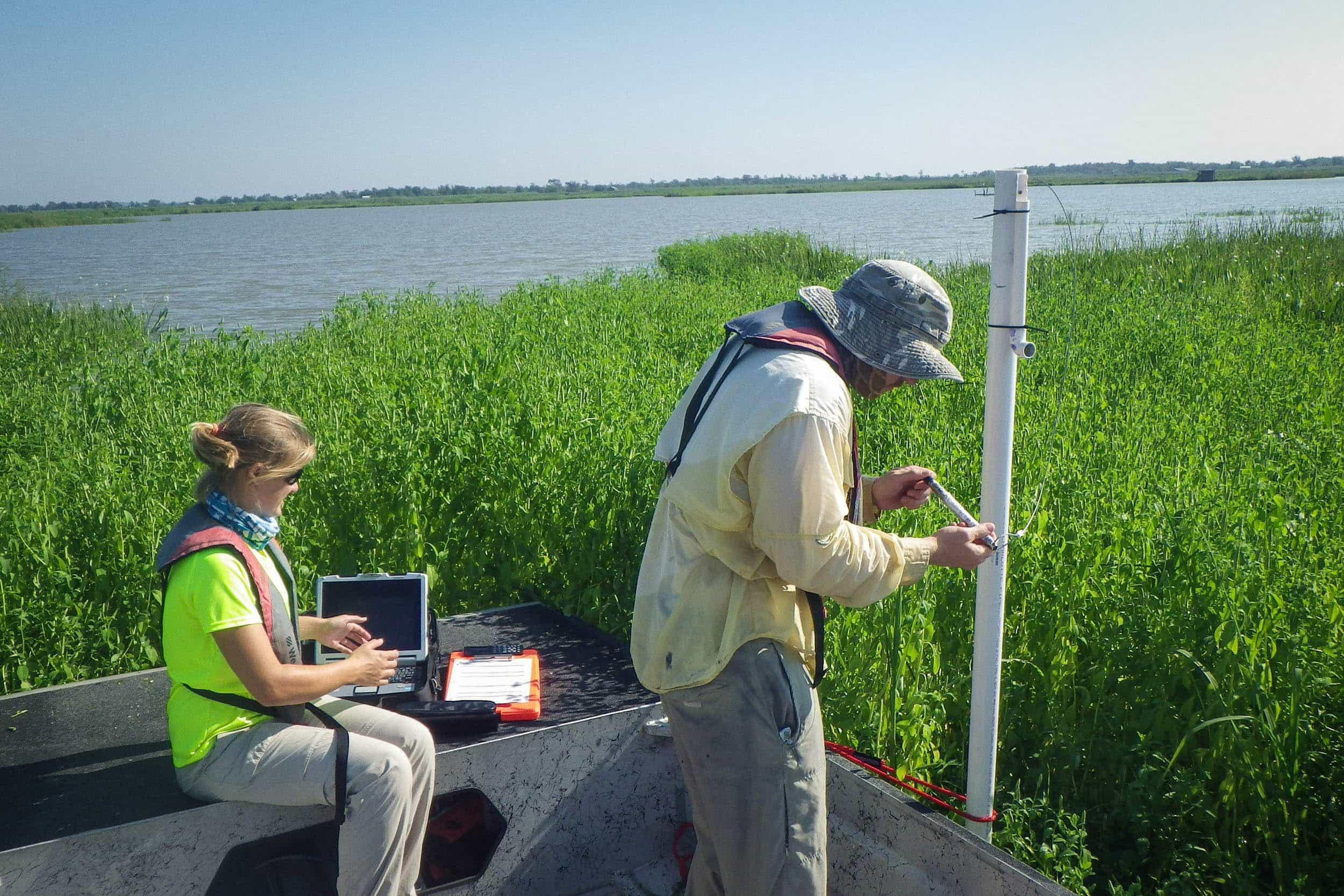 Anna Vallery and Tyler Swanson set up water quality monitoring equipment in the Trinity River