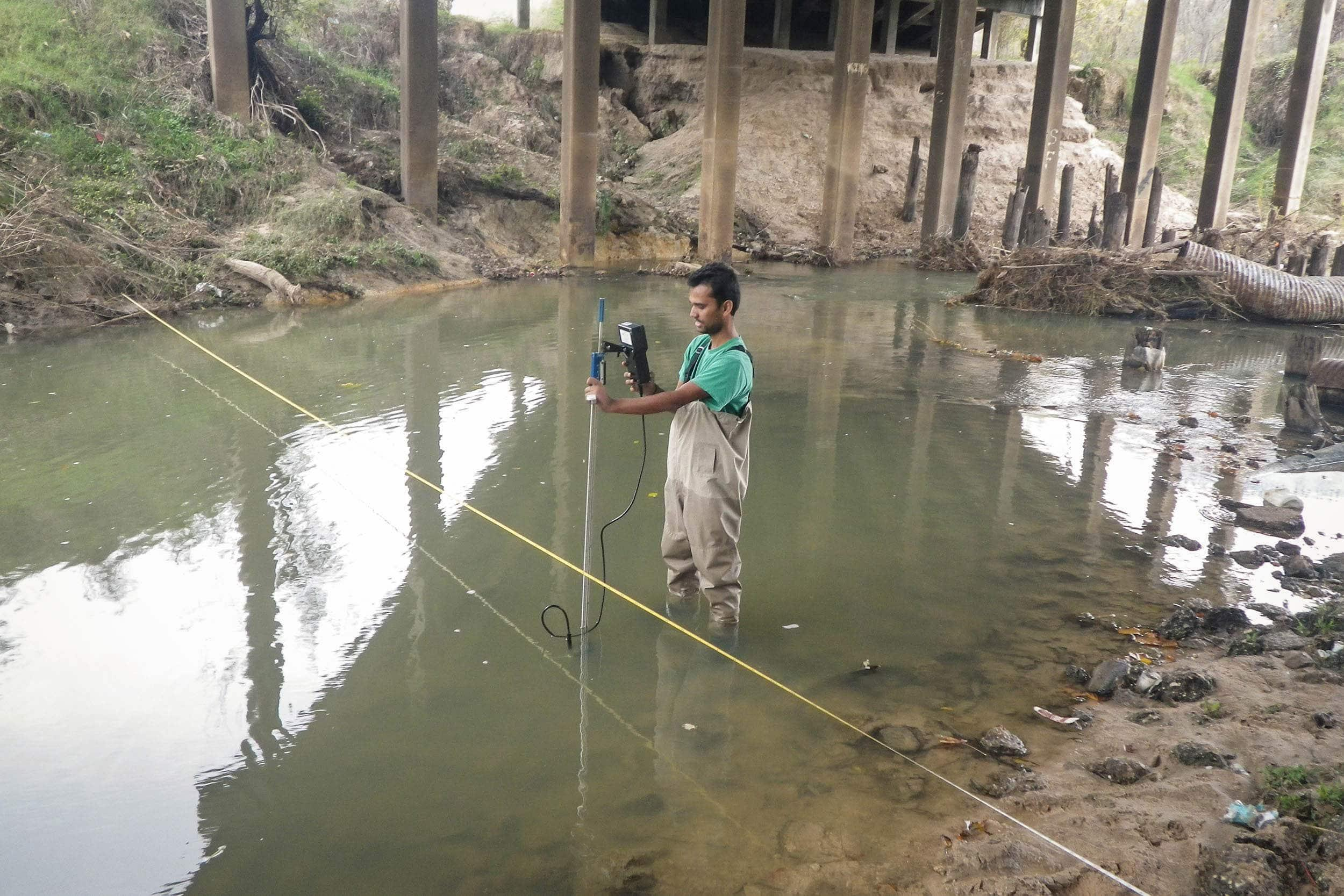 Khem Paudel uses the SonTek flow tracker to collect flow measurement data.