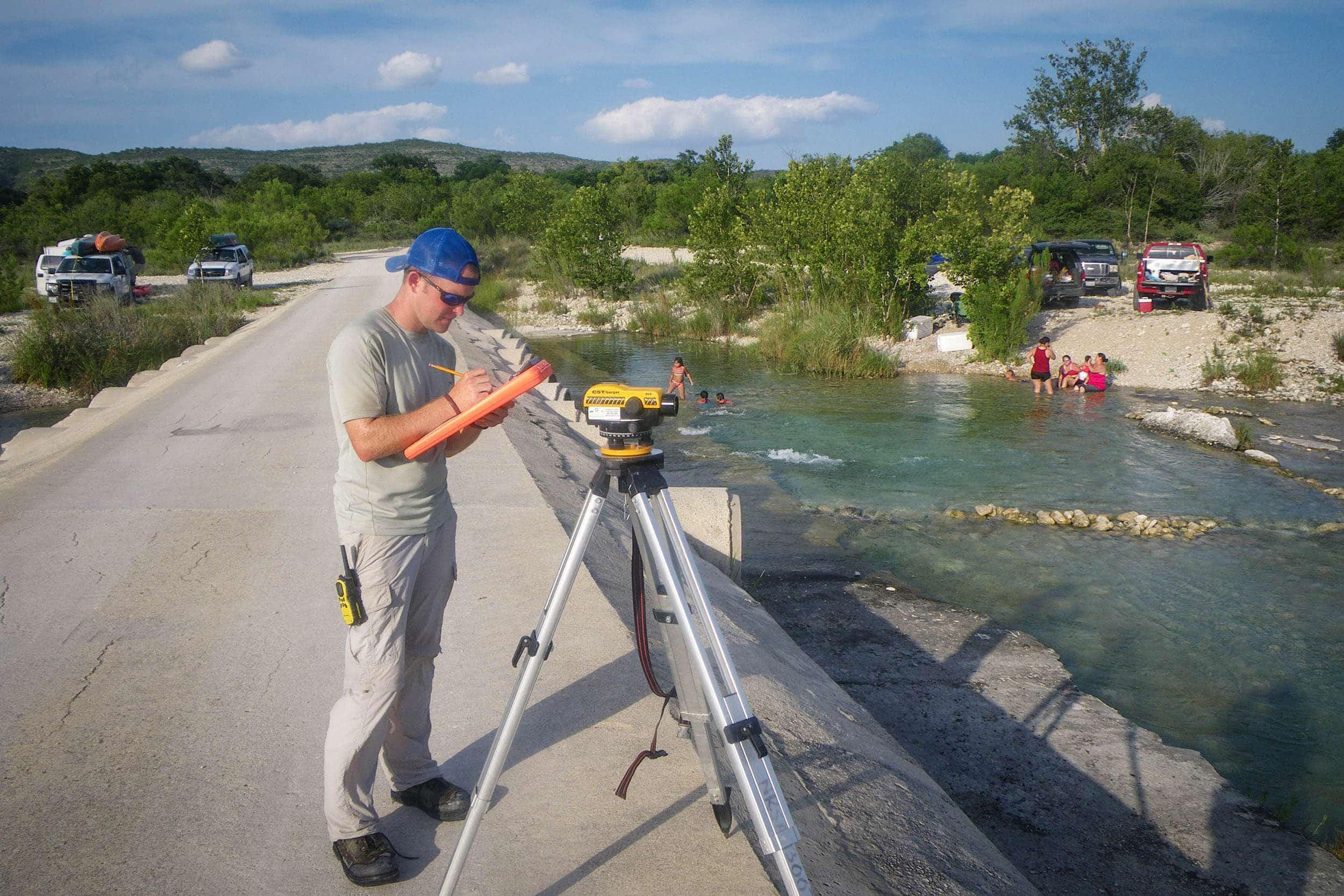 Stephen Curtis takes measurements at the Nueces River for the National Rivers and Streams Assessment.
