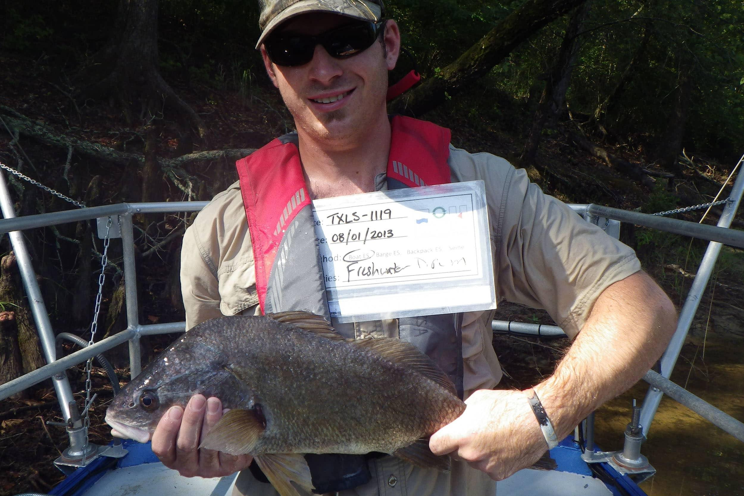 Michael Lane, research assistant, holding a freshwater drum, collects fish community data for the NRSA project
