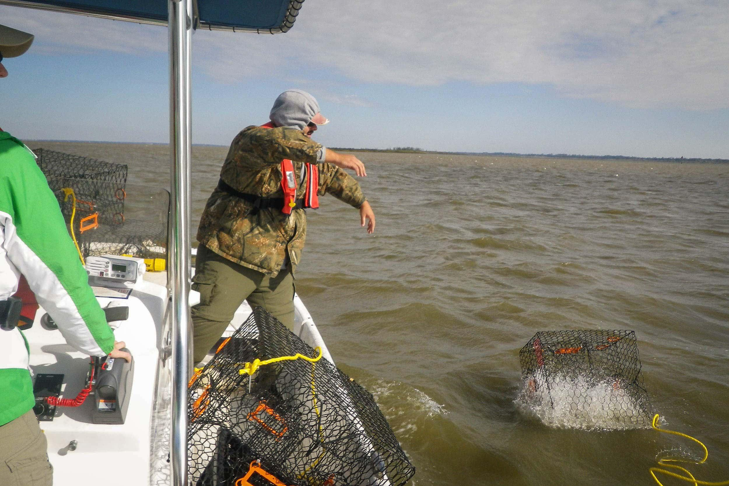 Bryan Alleman, EIH research assistant, deploys a deep water crab trap