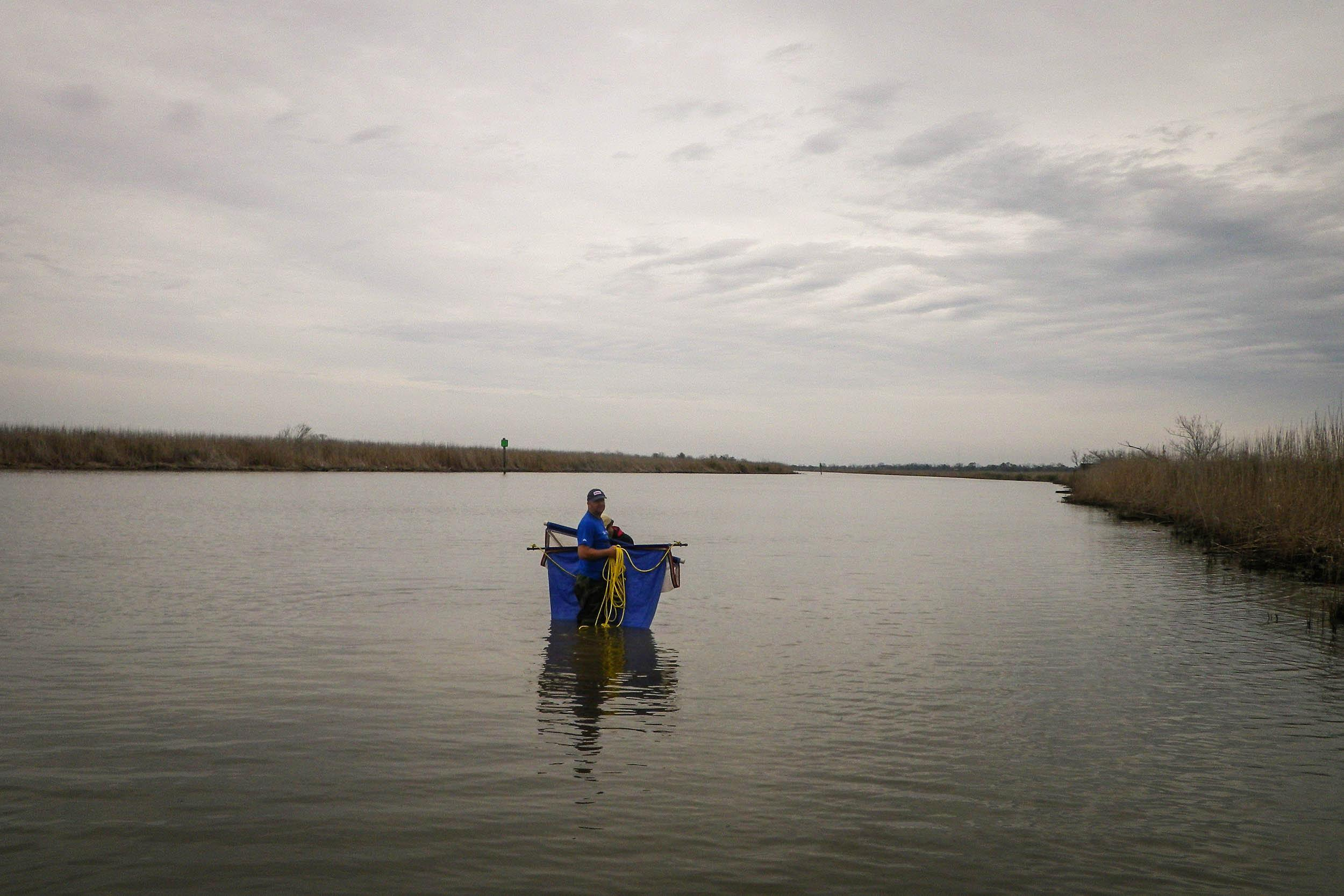 Colby Lawrence, research associate, uses a beam trawl to sample for nekton in the Trinity River.