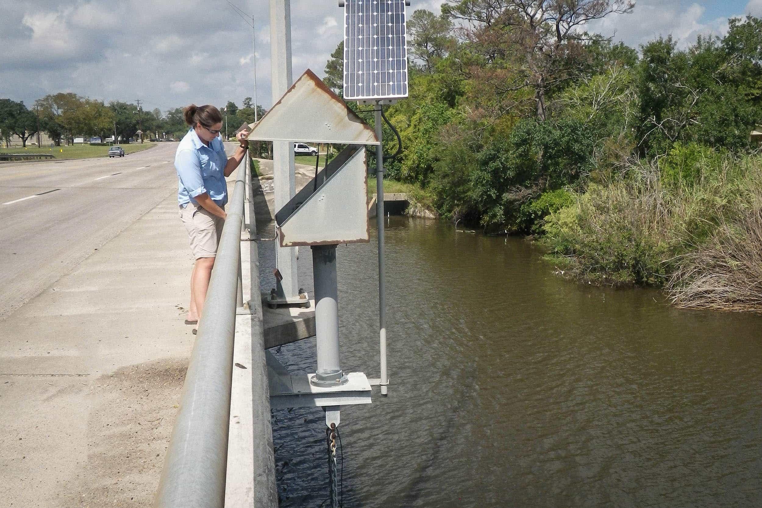 Misty Shepard, EIH research associate, collects water level (gauge height) data for Dickinson Bayou from a previously installed continuous monitoring TCEQ station.
