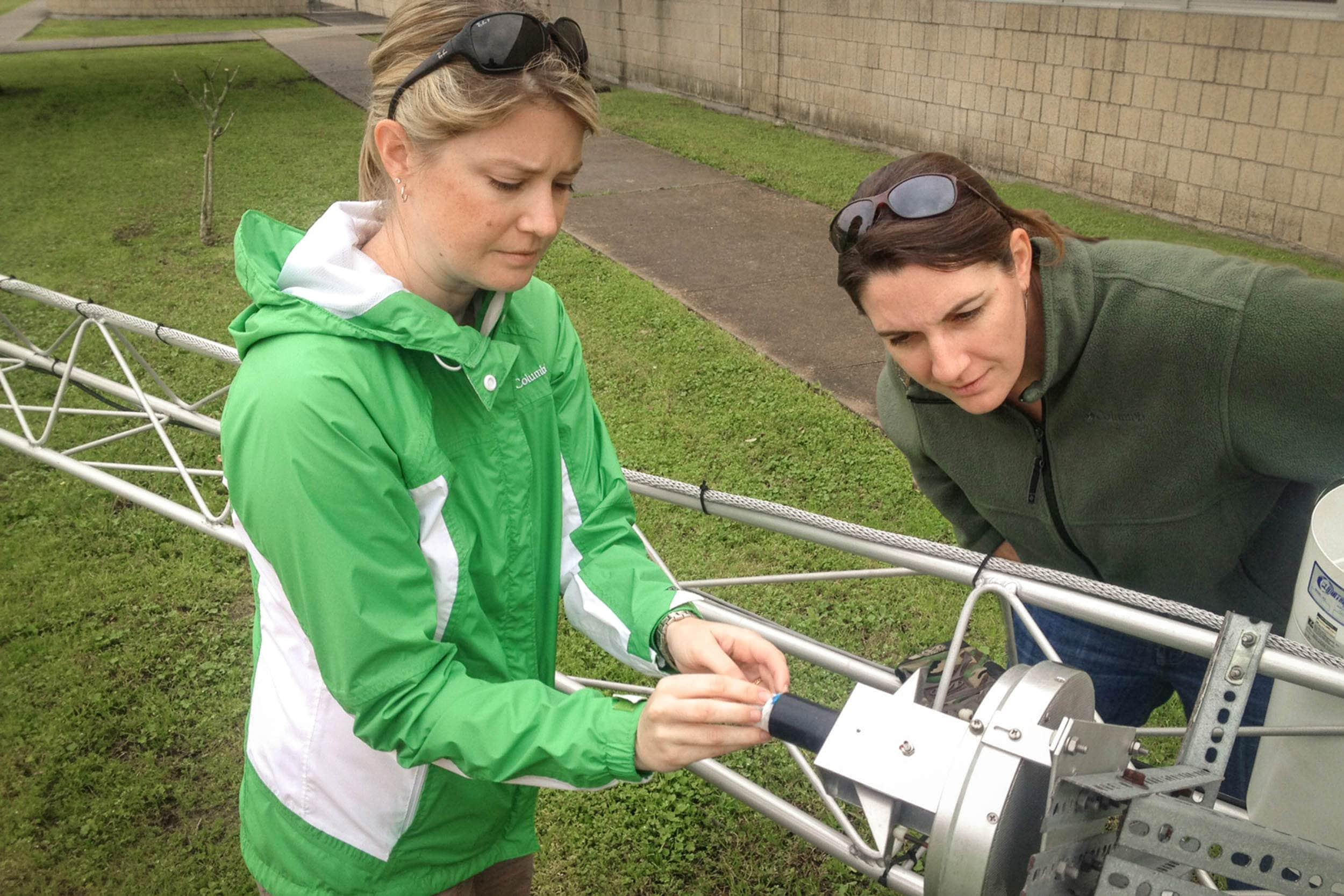 Jenny Oakley and Misty Shepard perform maintenance on the meteorological tower at Clear Brook High School.