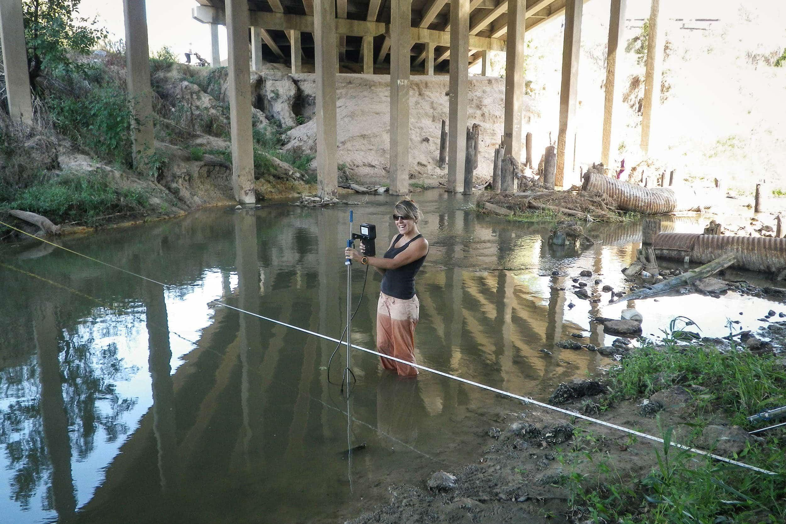 Laila Melendez, research assistant, takes flow measurements with the SonTek Flow Tracker at a Cypress Creek study site