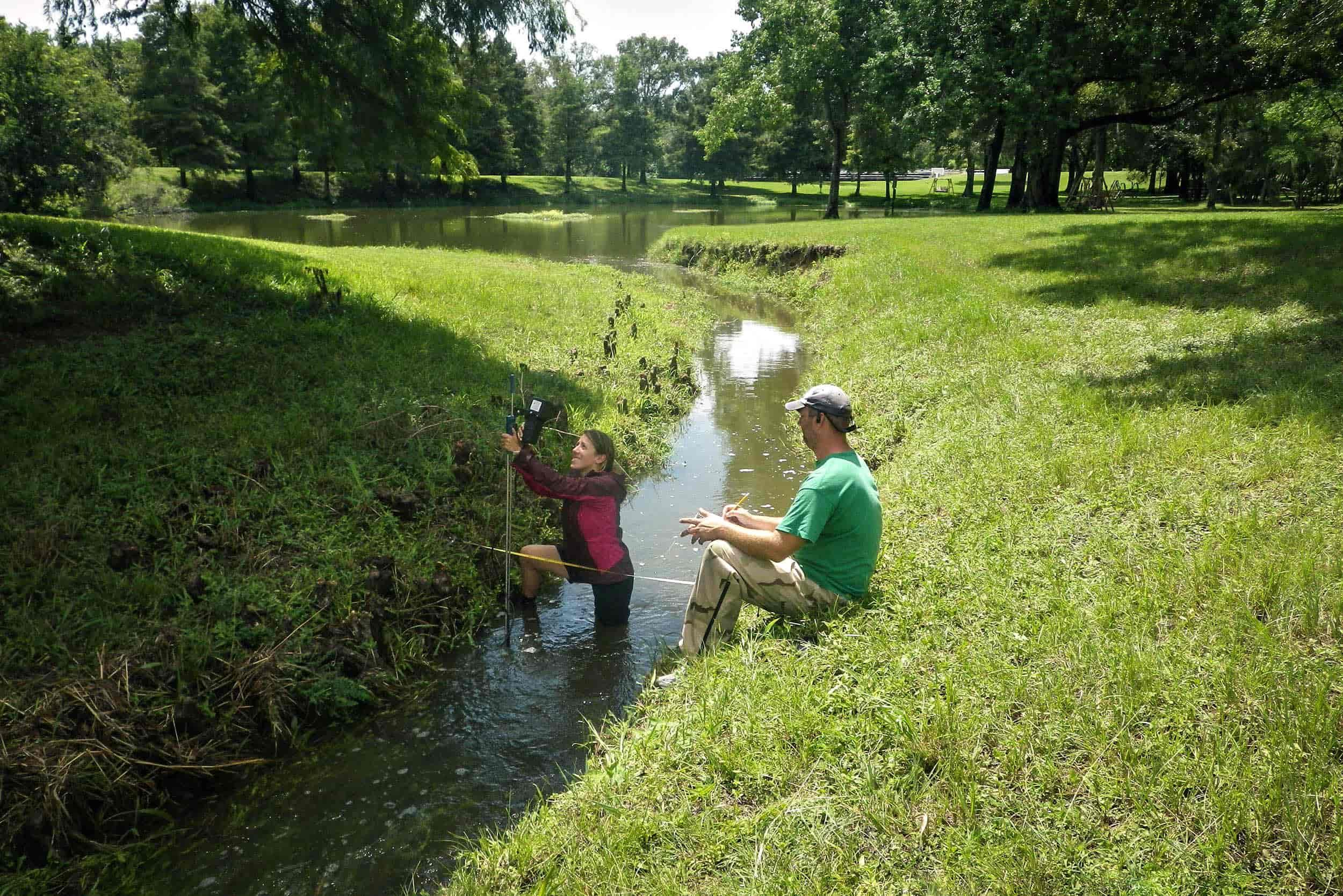 Laila Melendez, research assistant, and Colby Lawrence, research associate, take a flow measurement during a wet weather event.
