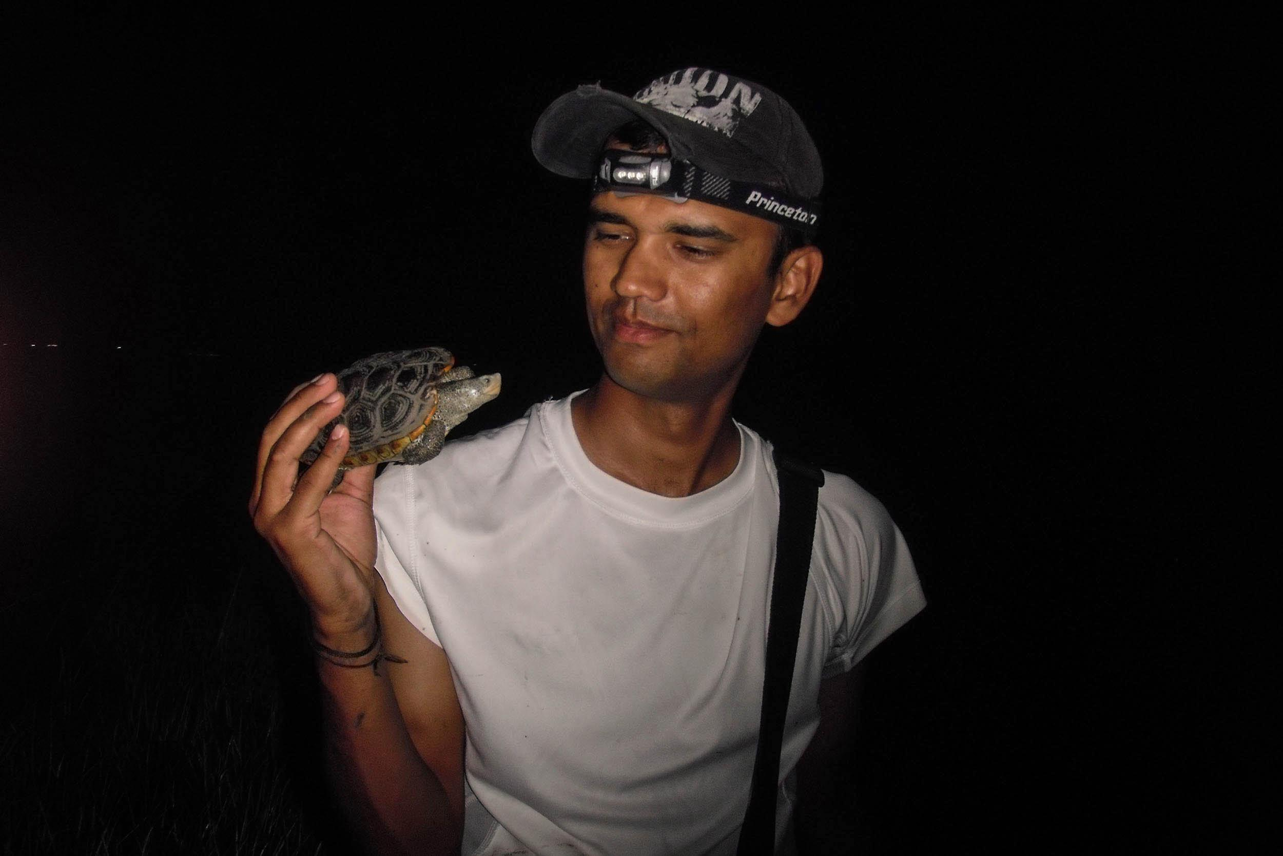 Khem Paudel, research assistant, holds a terrapin caught during a night survey