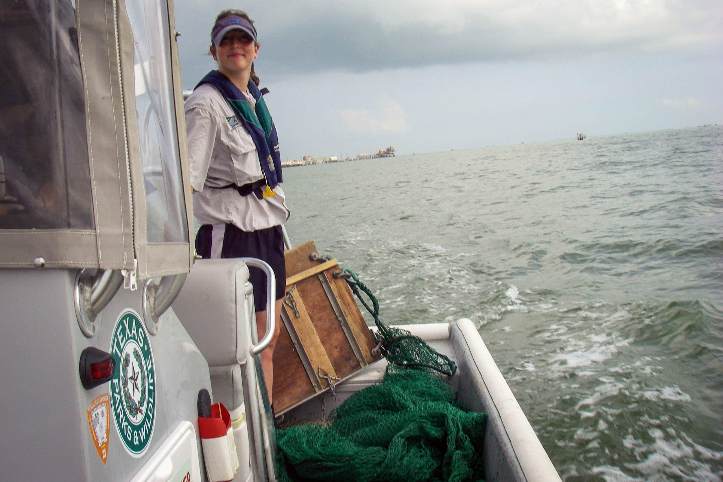 Danielle Crossen, research assistant, prepares to deploy a trawl from the TPWD boat